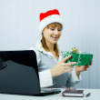 Working Girl in Santa hat with a gift — Stock Photo