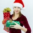 Beautiful smiling girl in Santa hat with presents — Stock Photo #4433961