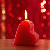 Red burning heart shaped candle — Stock Photo
