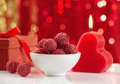 Raspberry truffles and burning candle — Stock Photo