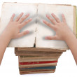 Royalty-Free Stock Photo: Hands above stacked old books of different shape and color.