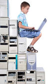 Boy plays with laptop a steps from old computers — Stock Photo