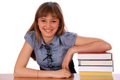 Girl sits at table and has put a hand on pile of books — Stock Photo