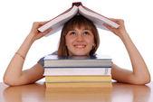女の子は頭の上の赤い本を保持します。 — ストック写真