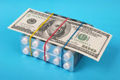 Hundred dollars lays on packing of white tablets — Stock Photo
