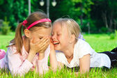 Two cute girls laughing on the grass — Stock Photo