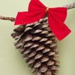 Holiday Pinecone with a Red Bow on a Green Background - Stock Photo