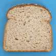 Slice of Whole Grain Bread on Vibrant Blue — Stock Photo