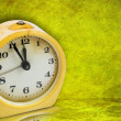 Stock Photo: Yellow clock on green background