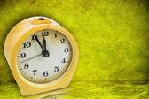Yellow clock on green background — 图库照片