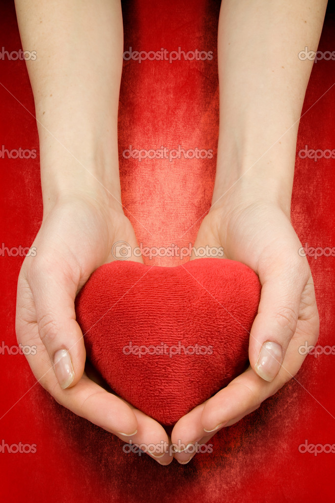 Hands with heart on red grunge background — Stock Photo #4735502