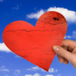 Hand with heart on sky background — Stock Photo