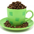 Green cup with coffee beans — Stock Photo