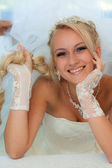 Bride smiling holding hair. — Stock Photo