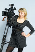 Blonde girl takes on professional video cameras. — Stock Photo