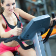 Stock Photo: Girl is cycling in fitness hall
