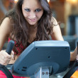 Girl is cycling in fitness hall — Stock Photo #4020532