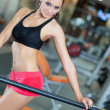 Girl with perfect body in fitness hall - Stock Photo