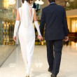 Bridegroom and bride walk in mall — Stock Photo