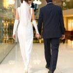Bridegroom and bride walk in mall — Stock Photo