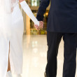 Foto Stock: Bridegroom and bride walk in mall