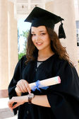 Young caucasian student in gown with watch — Stock Photo