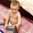 Stock Photo: Cute caucasian baby with vacuum cleaner