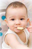 Cute caucasian baby eating — Stock Photo