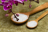 Spa essentials (bath salt in a spoon and flowers of orchids) — Stock Photo