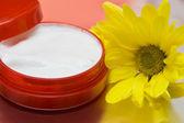 Cosmetic moisturizing cream with flower — Stock Photo