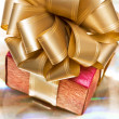 Stock Photo: Red gift box on golden background