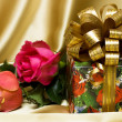 Gift box with flowers on silk background — Stock Photo