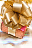 Red gift box on golden background — Stock Photo