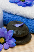 Cream, stones and towel with flowers — Stock Photo