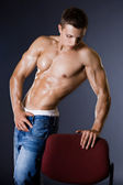 Young bodybuilder man on black background — Stock Photo
