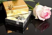 Gül desenli siyah arka plan üzerine hediye kutuları — Stok fotoğraf