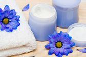 Spa essentials, cream and towel with blue flowers — Stock Photo