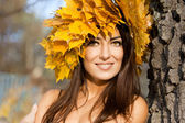 Woman with yellow leaves in autumn — Stock Photo