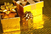 Festive gift boxes on golden background — Stok fotoğraf