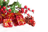 Gift boxes with pinecone and european holly — Стоковое фото