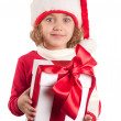 A small girl with a christmas hat and a present — Stock Photo #4401937