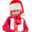A small girl with a christmas hat and a present — Stock Photo