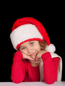 Cute girl in Christmas hat, dreaming — Stock Photo