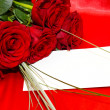 Red roses and invitation card — Stock Photo