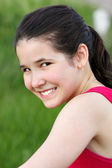 Spectacular smile of fresh female face over green grass — Stock Photo