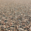 Uneven asphalt road with stones - Stockfoto