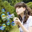 Young girl blowing soap bubbles in autumn park — Stock Photo #5327168