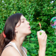 Young girl blowing soap bubbles in autumn park — Stock Photo #5329965