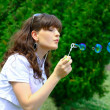Stock Photo: Young girl blowing soap bubbles in autumn park
