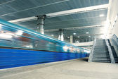 Blue moving train with staircase — Stock Photo